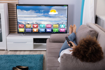 Woman Watching Television With Colorful Applications On Screen