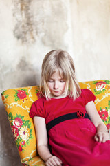 Little blonde girl in red dress sitting on floral armchair and looking downåÊ