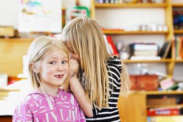 Two young girls gossiping