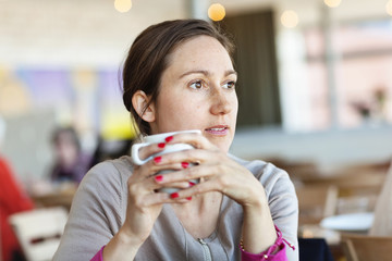 Portrait of young brunette woman drinking coffee