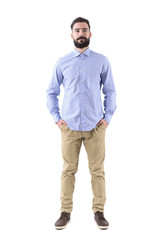 Front view of young beard smart casual business man with hands in pockets. Full body length portrait isolated on white studio background.