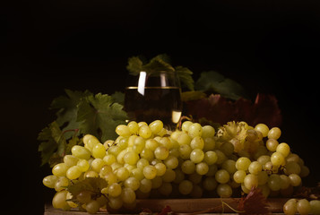 виноград белый лежит на чёрном фоне