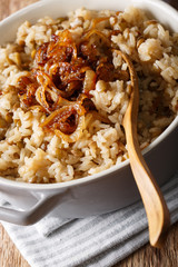 Vegetarian Mujaddara from rice and lentils with caramelized onion macro. vertical