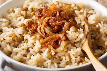 Arab food: Mujaddara from rice and lentils with caramelized onion close-up. horizontal