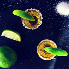 Gold Mexican tequila with lime and salt on dark table. Top view, flat lay, toned image