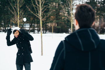 Young interracial couple having snowball fight in a park