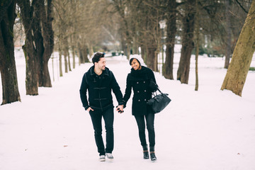Interracial couple walking in a snowy park