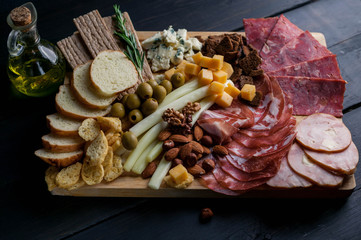Assorted from meat and cheese on a chopping board. Smoked sausage, meat roll from a turkey with cheese, jamon, olives, nuts and various grades of cheese. Mediterranean traditional snack.