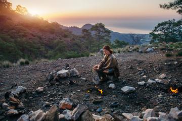 Female traveler sitting on rock near Chimeara fires in Cirali