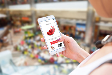 Shopping online with mobile phone. Woman holding smart phone. Shoes on app or web site. Shopping mall in background.