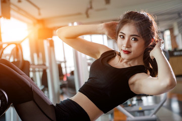 Asian woman exercising in the gym, Young woman workout in fitness for her healthy and office girl lifestyle. She is sit up position.