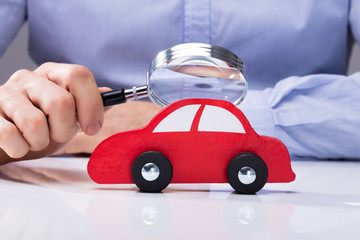 Person Looking At Car Through Magnifying Glass