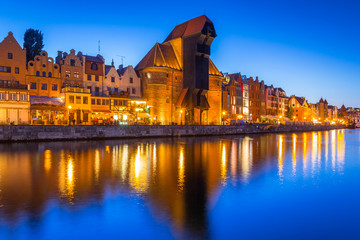 Gdansk at night with historic port crane reflected in Motlawa river, Poland