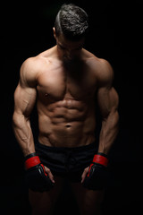 Muscular fighter posing in front of black background
