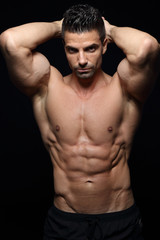 Bodybuilder posing in front of black background