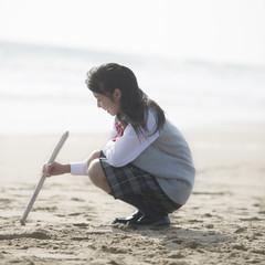 砂浜に絵を描く女子校生