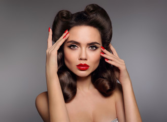 Pin up girl with red lips makeup, manicure nails and retro curls hair style. Retro woman looking at camera holds fingers near the head. High fashion photo. Sexy female portrait.