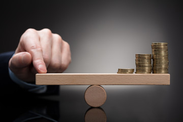 Finger Balancing Stacked Coins On Seesaw
