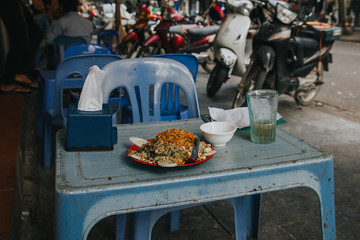 Vietnamese street food on dirty blue plastic table.