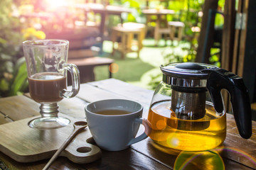 The morning coffee has been drunk. There is a wooden spoon on the plank, a glass of tea and a golden tea pot on the side of the old wooden table. A coffee shop in the garden. Sunlight light