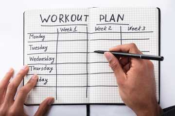 Person Filling Workout Plan In Notebook