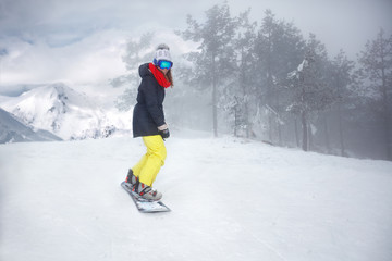 Female snowboarder on snowboard on mountain
