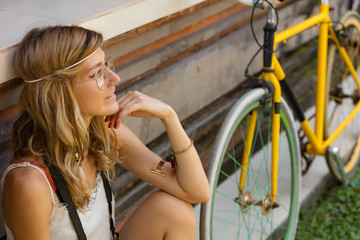 Pretty woman sitting with old bicycle outdoors.