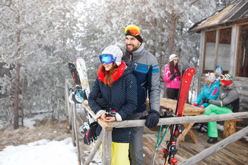 Skiers couple in winter wooden house