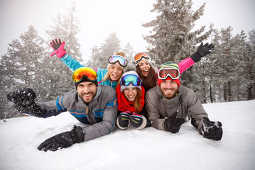 Cheerful friends on skiing laying together on snow