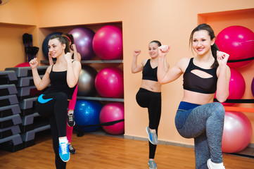 Beautiful women exercising aerobics in fitness club