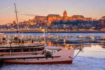 Illuminated boat against Royal palace in Budapest