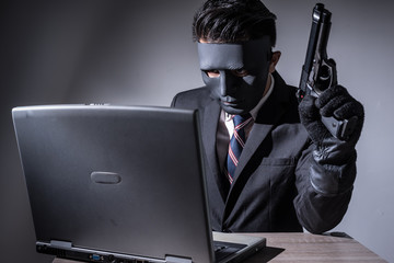 The abstract image of hacker or criminal wear a mask and suit using a laptop and hold a gun by another hand in the empty room. the concept of cyber attack, crime, virus, mafia, and cyber security.