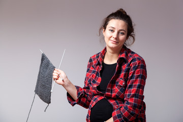 Young dark-haired married woman in plaid shirt is tired knit with knitting sweater from natural wool on gray isolated background