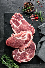 Fresh steaks from Raw pork meat on dark stone background, Top view