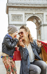 happy mother and daughter in Paris, France eating macaroons