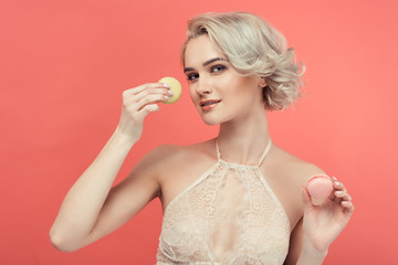 Aluminium Prints Macarons beautiful blonde woman with two delicious macarons, isolated on red