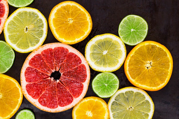 top view of slices of citrus fruits on black background