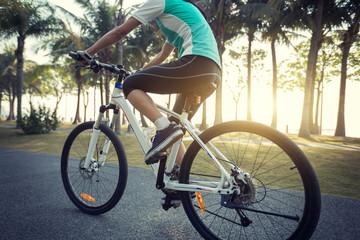 female cyclist riding bike in tropical park