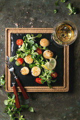 Fried scallops with lemon, cherry tomatoes and green salad served on wooden black slate serving board with cutlery and glass of white wine over old dark metal background. Top view, space