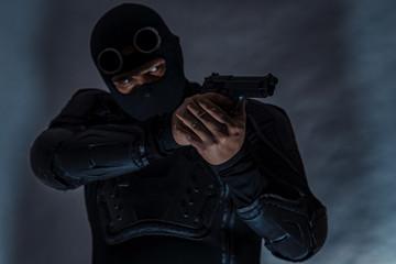 Armed spy in bulletproof vest. Hands hold a gun.