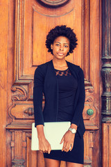 Young African American Businesswoman with afro hairstyle working in New York, wearing black fashionable clothes, wristwatch, holding laptop computer, standing by vintage office doorway, looking at you