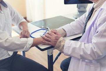 Doctor reassuring his holding hands for comfort patient which talking Symbol of support and trust in medicine after operation at hospital concept