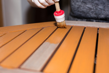 Woman strokes a wooden table with fresh paint