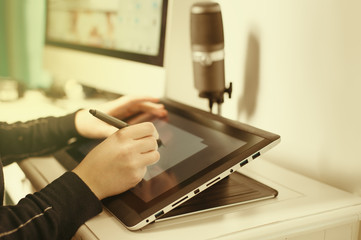 Drawing, photography and retouching on a computer laptop using a digital tablet and stylus pen.