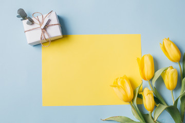 Mother's Day Composition: Yellow tulips, blank with copy space and a gift boxes on a blue background. Top view.Flat lay.