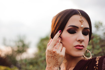 Mehendi on the hands of girls, Woman Hands with brown mehndi tattoo. Hands of Indian bride girl with brown henna tattoos.