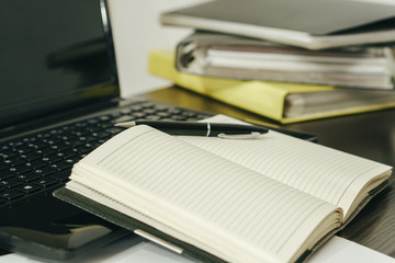 Office tools and accessories. The pen lies on the blank sheets of the notebook beside the keyboard.