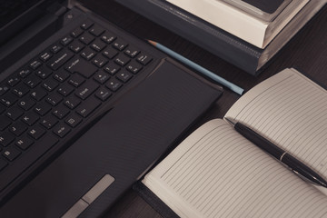 An open notepad with clean pages lies next to the laptop.