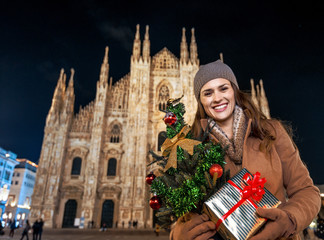 smiling woman with Christmas tree and gift in Milan, Italy