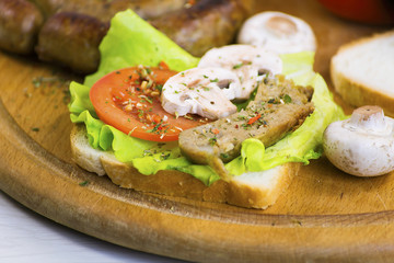 homemade sausage and sandwich with sausage, mushrooms and tomato